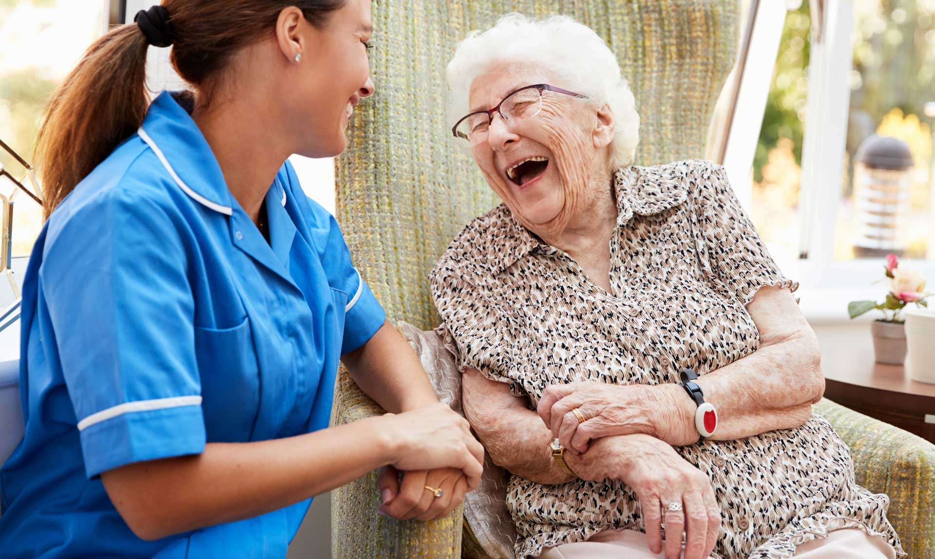 a nurse and an elderly woman laughing
